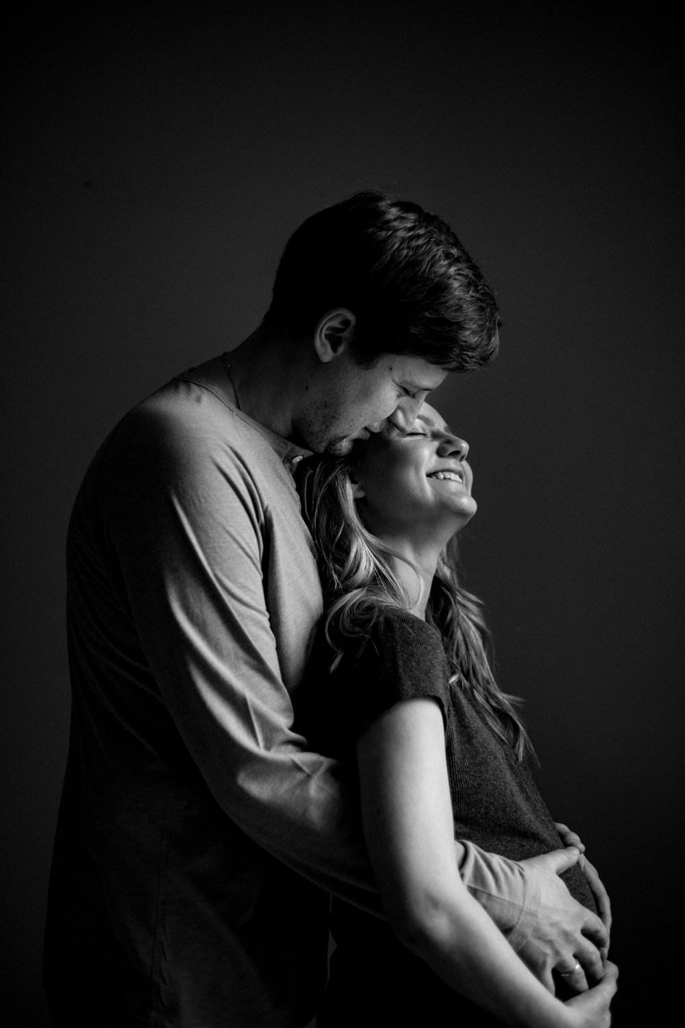 Indoor maternity session where man kisses pregnant wife by Huntsville and Madison Alabama maternity photographer Rachel K Photo