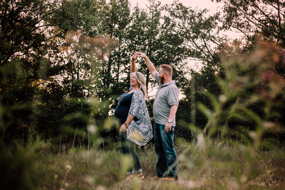 Man and pregnant woman dancing in field by Huntsville and Madison Alabama maternity photographer Rachel K Photo