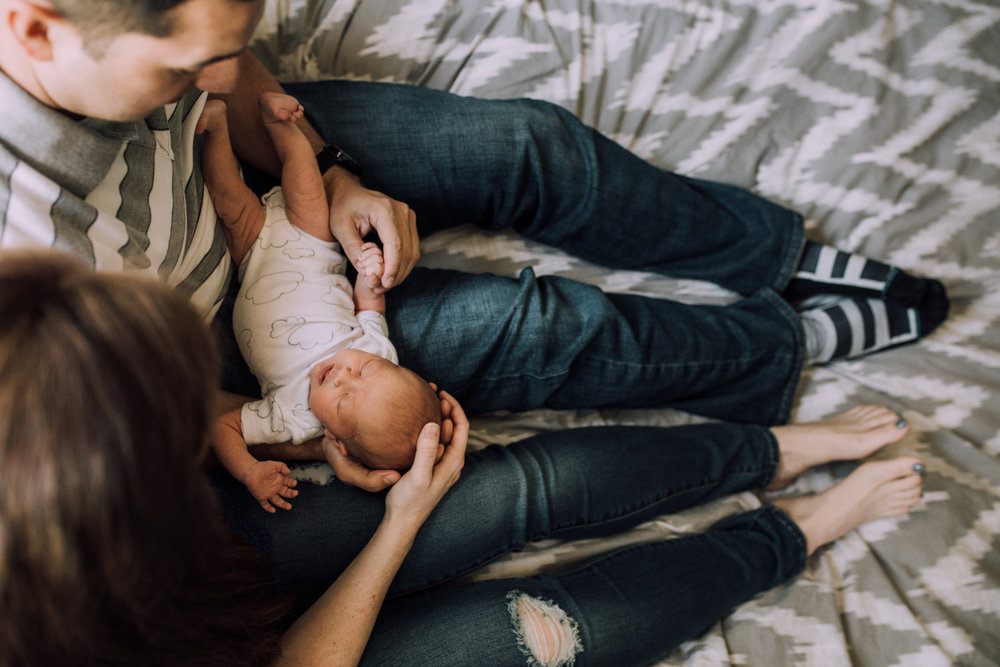 Baby being held by mom and dad on bed from Huntsville Alabama lifestyle newborn session