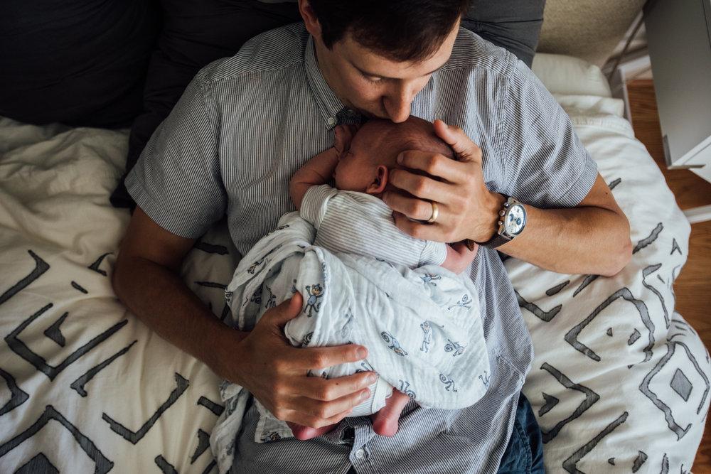 Dad kisses sleeping newborn baby from Huntsville and Madison Alabama lifestyle newborn photographer Rachel K Photo