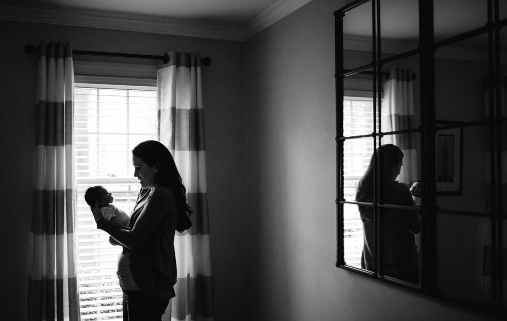 Mom looks at newborn in front of window from Huntsville and Madison Alabama lifestyle newborn photographer Rachel K Photo