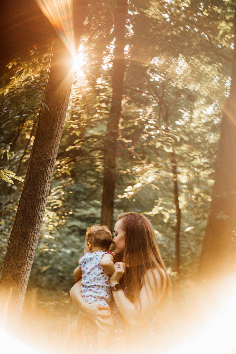 Mom kisses toddler in wooden sunlit photo from Madison and Huntsville Alabama family photo session.