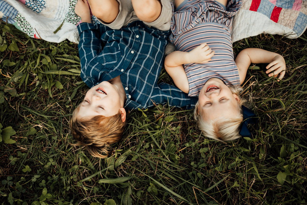 Two kids lay in grass laughing by Madison and Huntsville Alabama family photographer Rachel K Photo