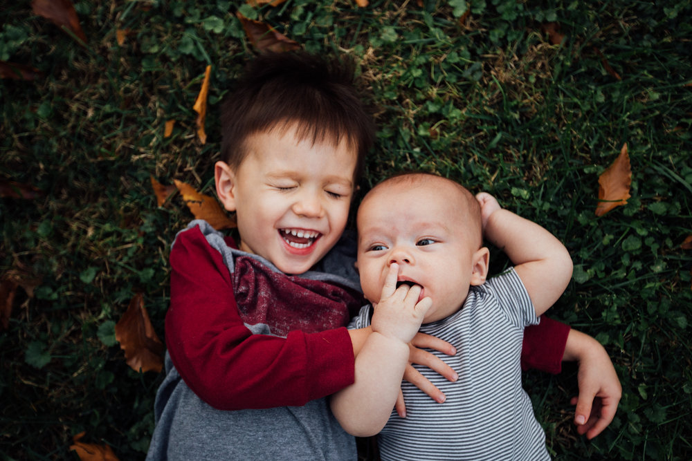 Toddler laughs with baby by Madison and Huntsville Alabama family photographer Rachel K Photo