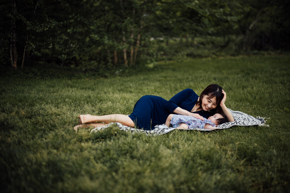 Mother lays with baby in grass by Madison and Huntsville Alabama family photographer Rachel K Photo