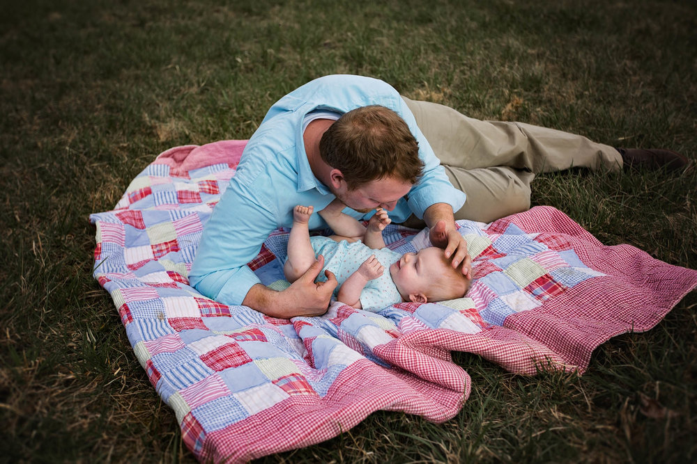 Father lays with baby daughter on blanket by Madison and Huntsville Alabama family photographer Rachel K Photo
