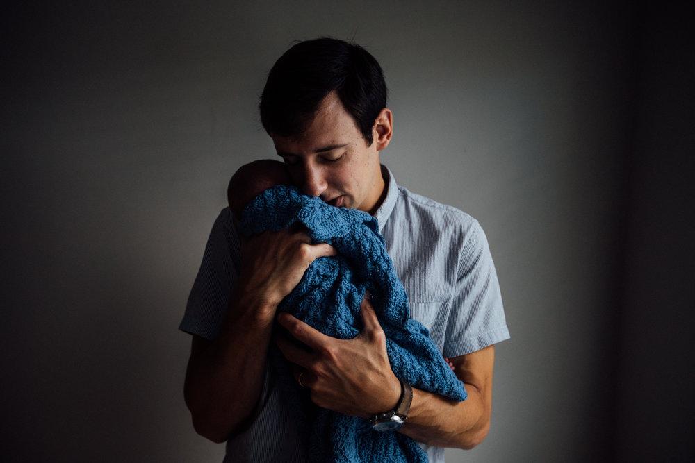 Father comforts newborn in blue blanket from Huntsville and Madison Alabama lifestyle newborn photographer Rachel K Photo