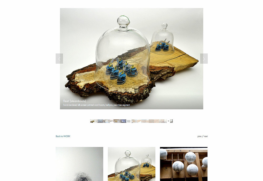sculpture of paper boats within a bell jar