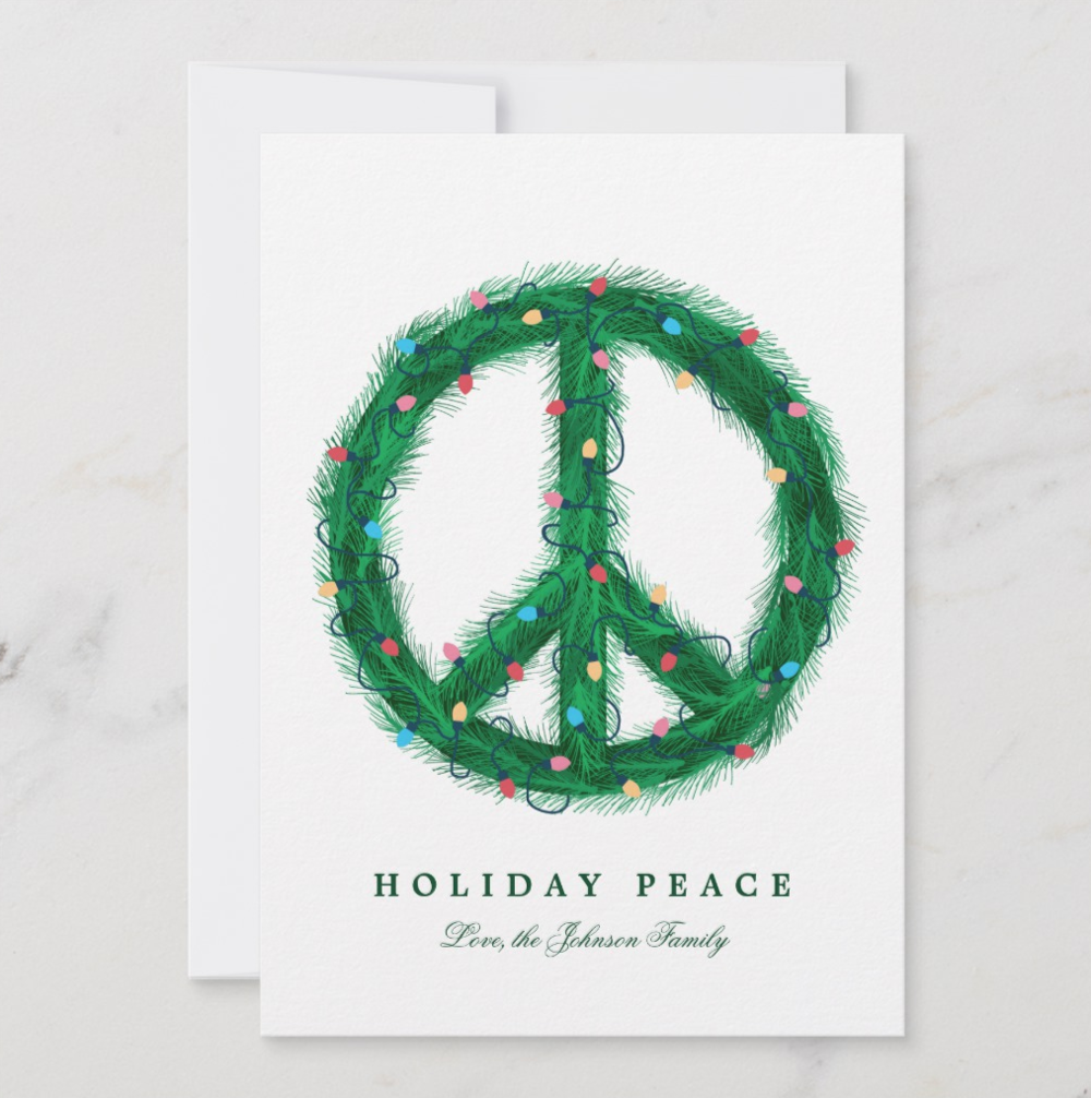 A festive alternative to the traditional holiday card, this pine wreath peace symbol is wrapped with colorful string lights and Christmas cheer.   Peace Wreath by Bah Humbug Design
