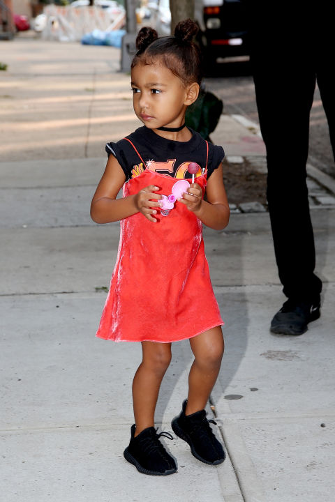 North West, daughter of Kanye and Kim Kardashian West, walks the NYC streets rocking this '90s inspired play-outifit and rocking her dad's Yeezy's.