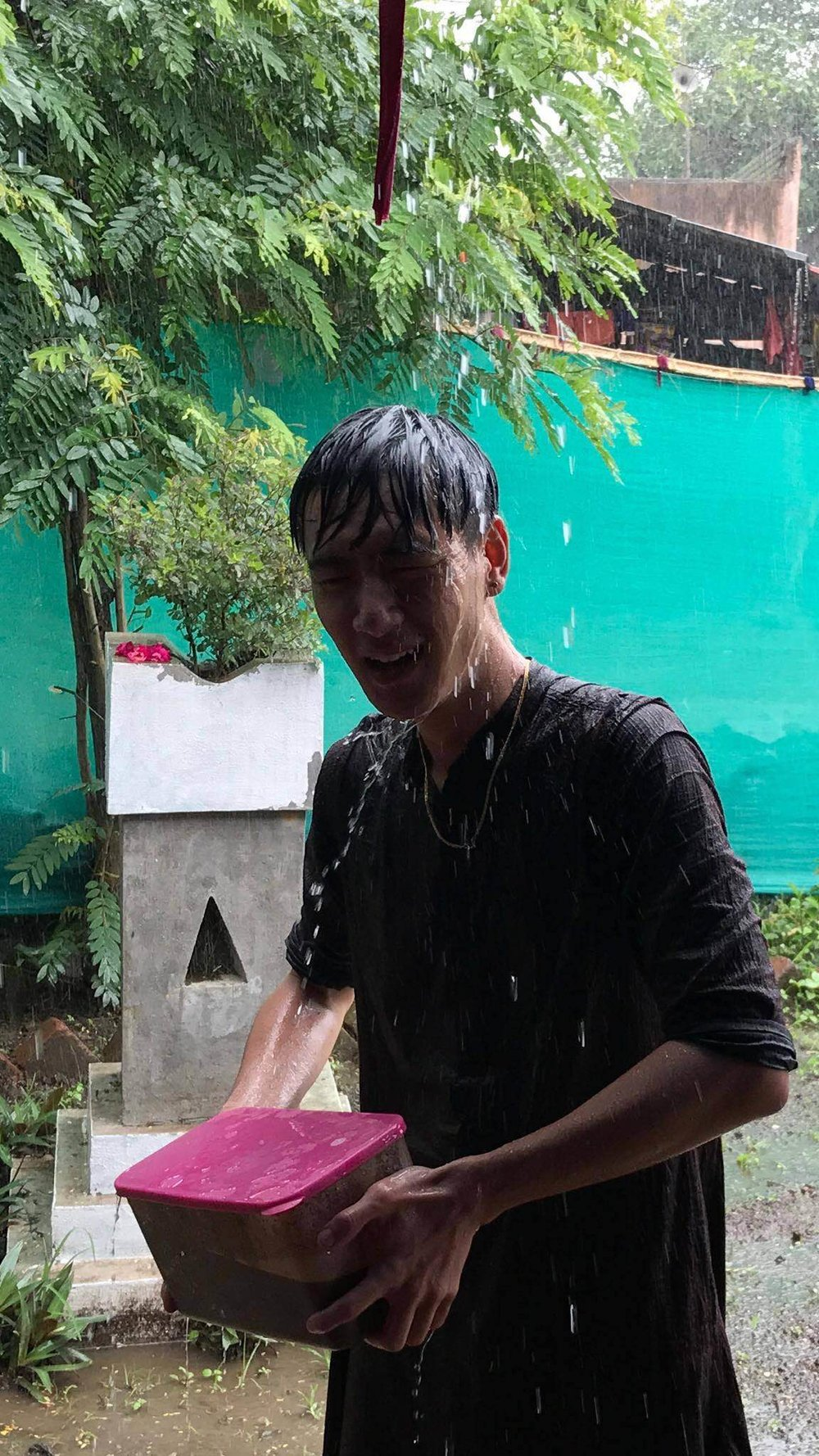 Michael caught in a monsoonal downpour, after assisting Sudam in the fields all day.