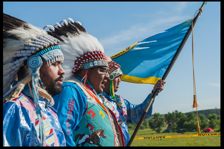 Darrin Old Coyote, chairman of the Crow Nation, enters a prayer camp with Nigel Stewart, left, and Taylor Real Bird, right, both Crow tribal members and U.S. military veterans, to offer support to the Standing Rock Sioux' fight against the Dakota Access pipeline. The Crow and Sioux nations were once enemies, and Old Coyote's appearance was considered a historic event by many in attendance. (Photo courtesy High Country News)