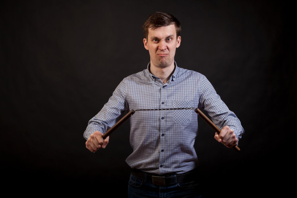"""Dark-haired man in a plaid shirt """"nholds a nunchuck  in his hands """"non black isolated background"""