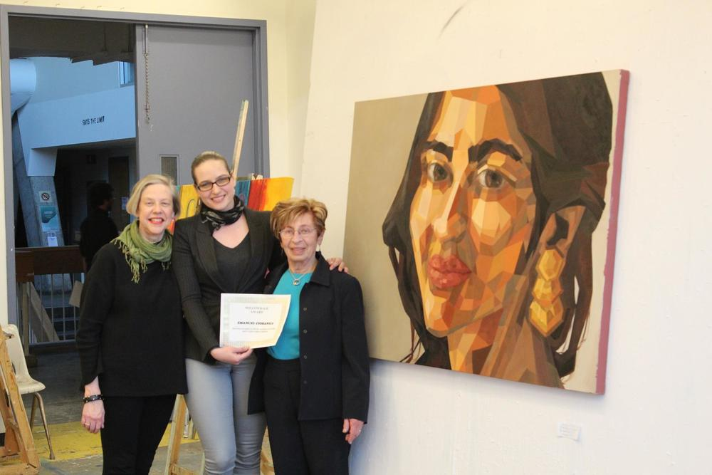 Professor Janet Jones (left) and Willowdale Group of Artists member Margie Wagner (right) standing with Emanuel Ciobanica beside her painting, facets of personality, at York University's Visual Arts Open House on April 15, 2015.