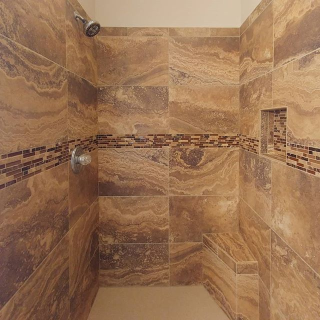 What makes this a beautiful install? The symmetry? The intentionality of tile placement? The smooth transition from field tile to accent band? They all work together to create a truly artful space.  #shower #accentband #accenttile #mosaic #porcelain #masterbath #schluter #schlutersystems