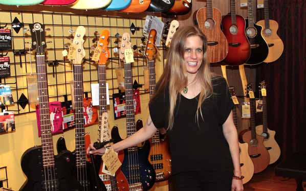 "In the music store called ""St. Frank's Music"", manager Deanna Phelps shows some the guitars for sale."