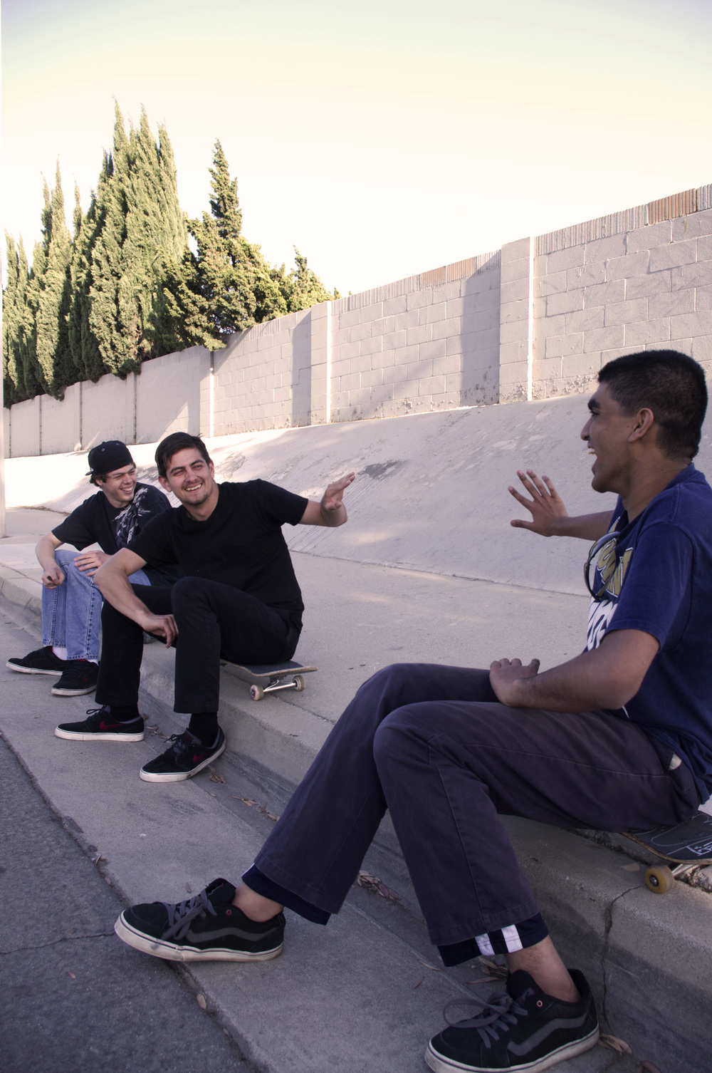 Team members Brandon, Adam, and Mohammed chilling at a skate spot.