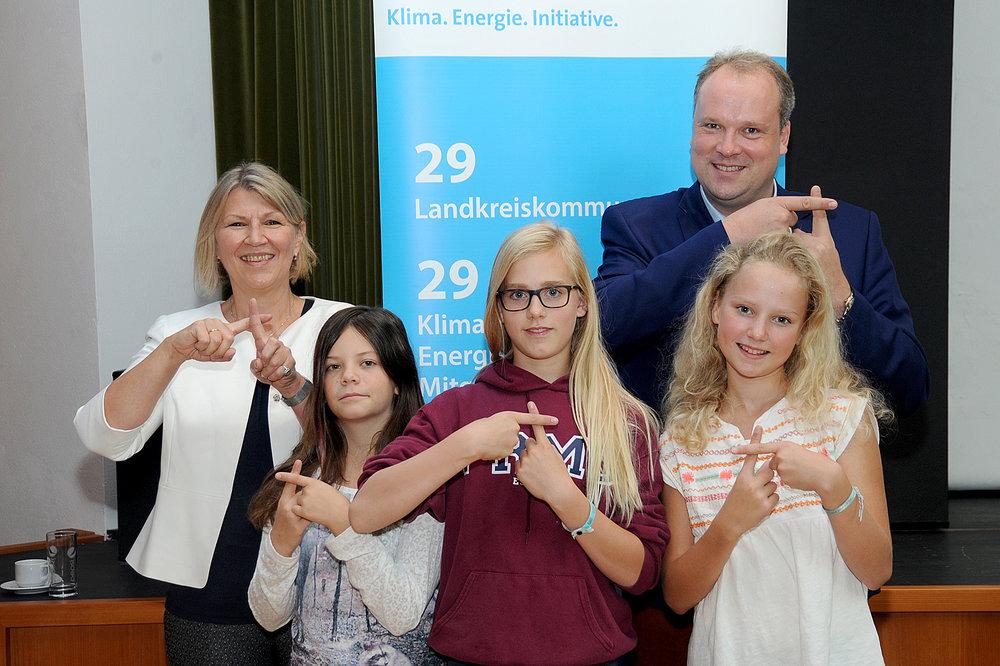 Ein Plus für mehr Klimaschutz im Landkreis: die drei Schülervertreterinnen des Pater-Rupert-Mayer-Gymnasiums Pullach mit Klassenlehrerin Linda Hofmann und Landrat Christoph Göbel.