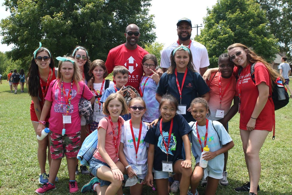 (top) torry holt and (bottom) both torry and terrence holt, surrounded by camp kesem attendees; Photos courtesy of Camp Kesem / N.C. State Chapter.