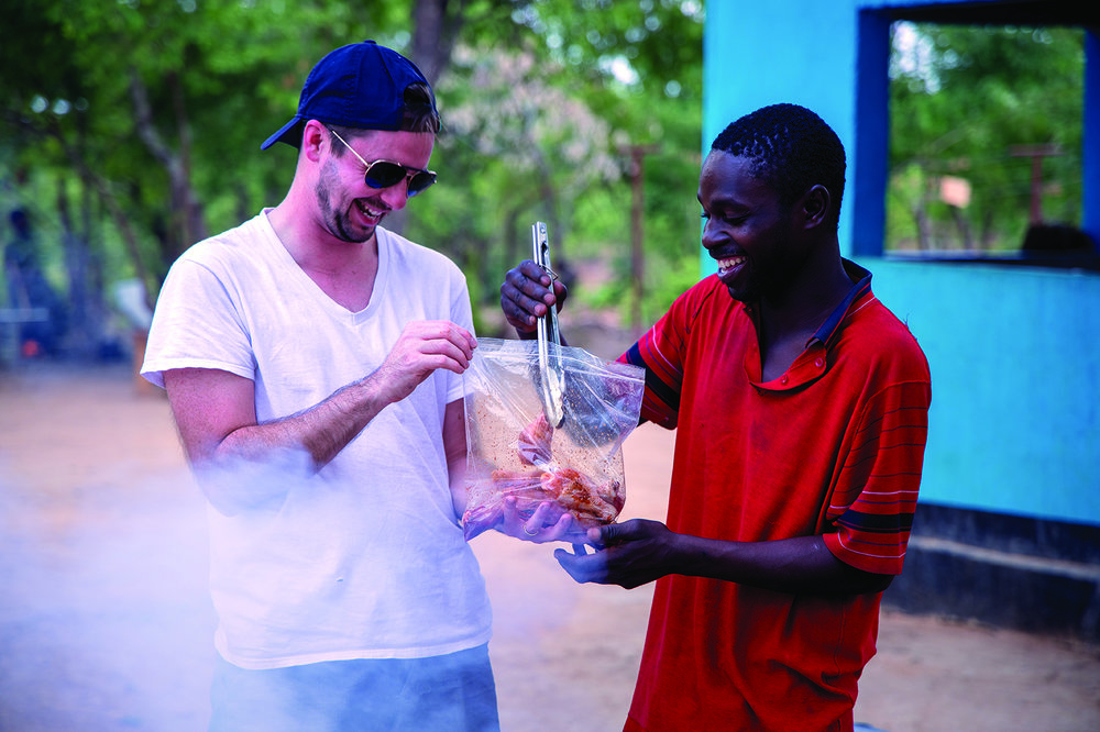 Longtime supporter, Carson Matthews, and Kunchubwi friend, Andrew, get ready for a braai (cookout).