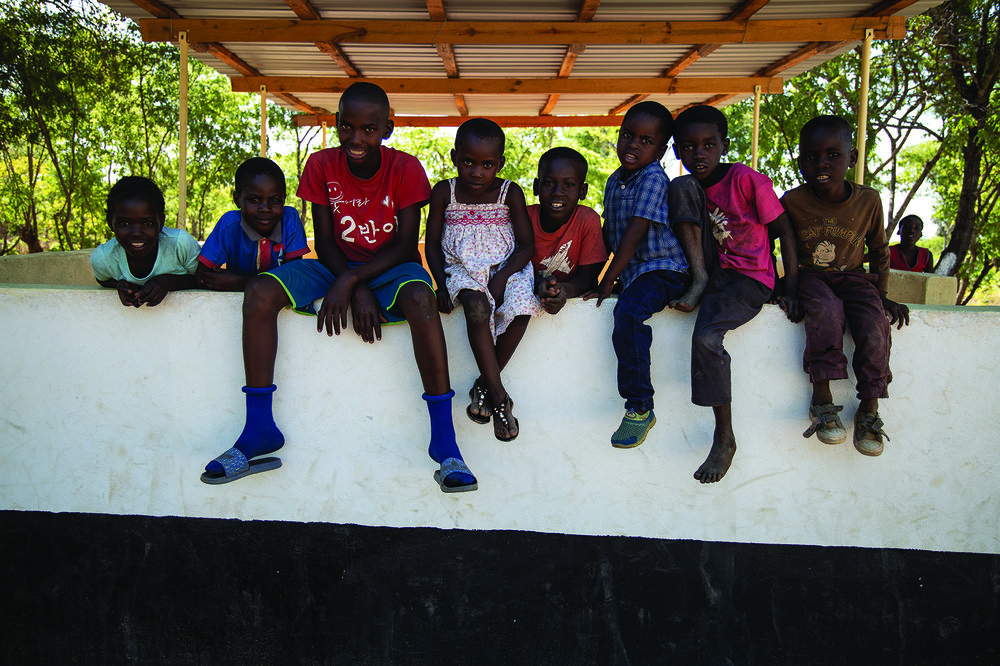 Village children wait for an afterschool program at the Love Abounds community playground and picnic shelter.