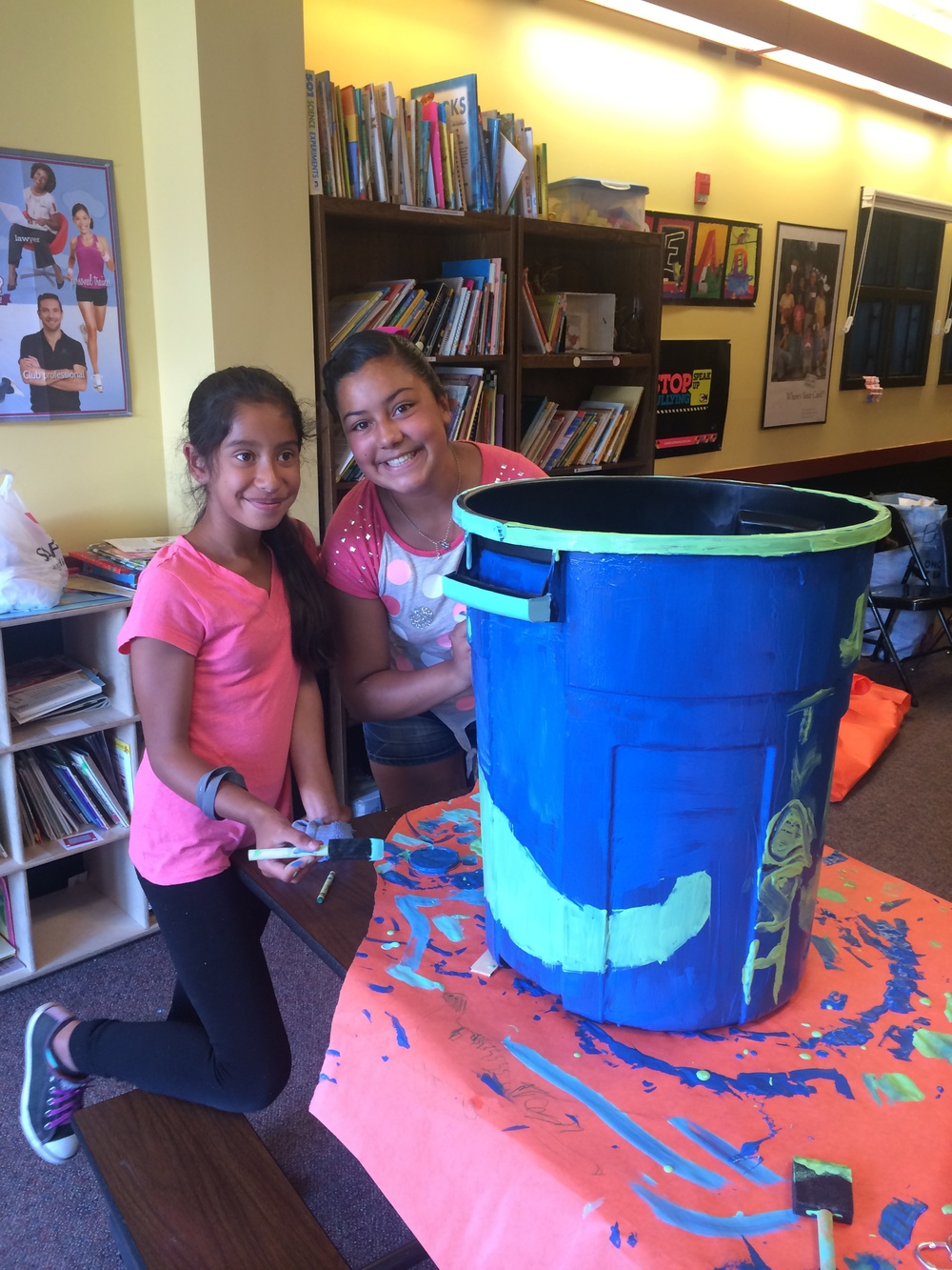 Two club members smile as they finish decorating their recycling bin