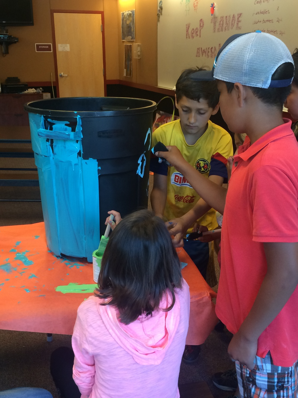 These club members are focused and hard at work decorating their recycling bin with detail