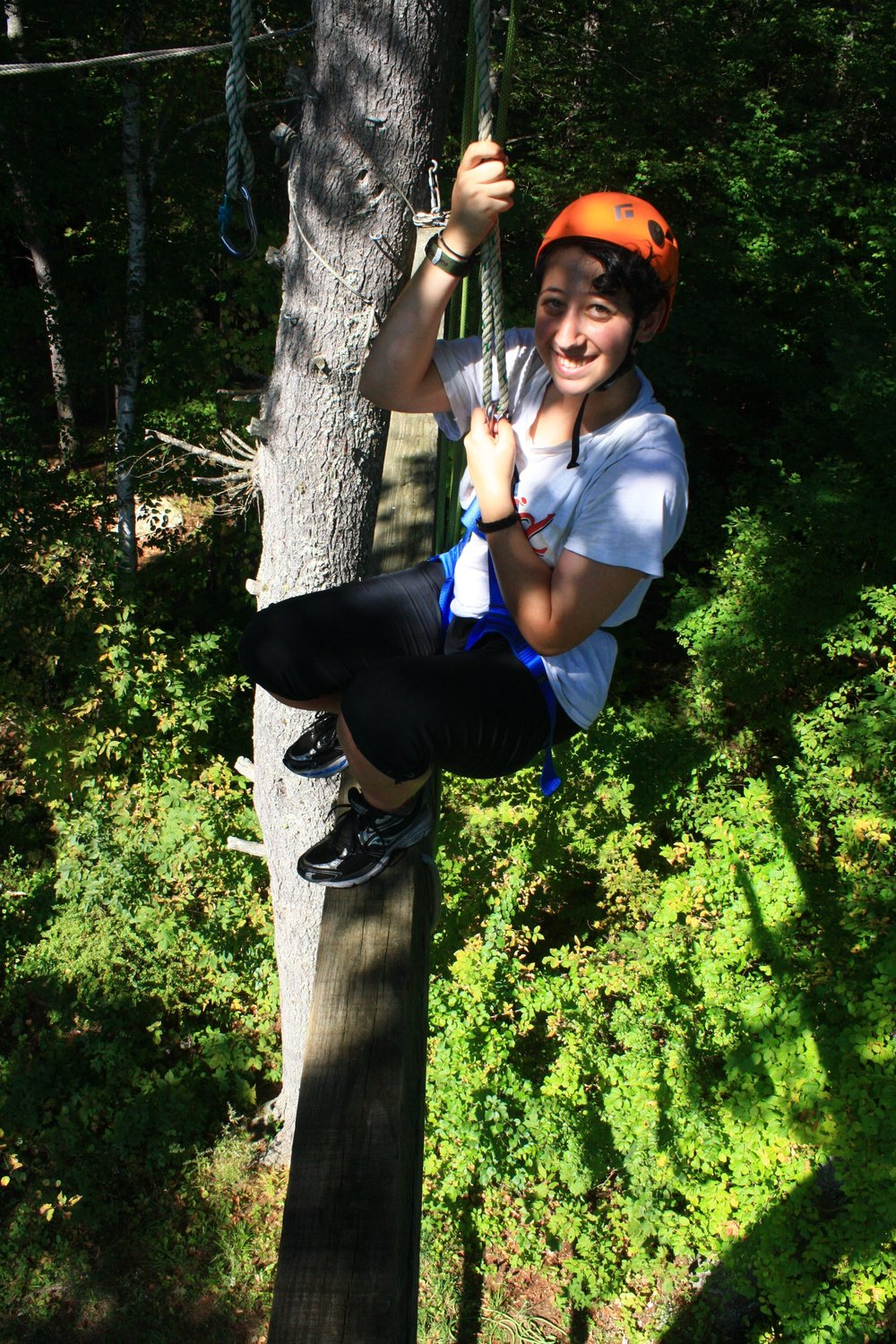 Xander up high in the trees on the ropes course