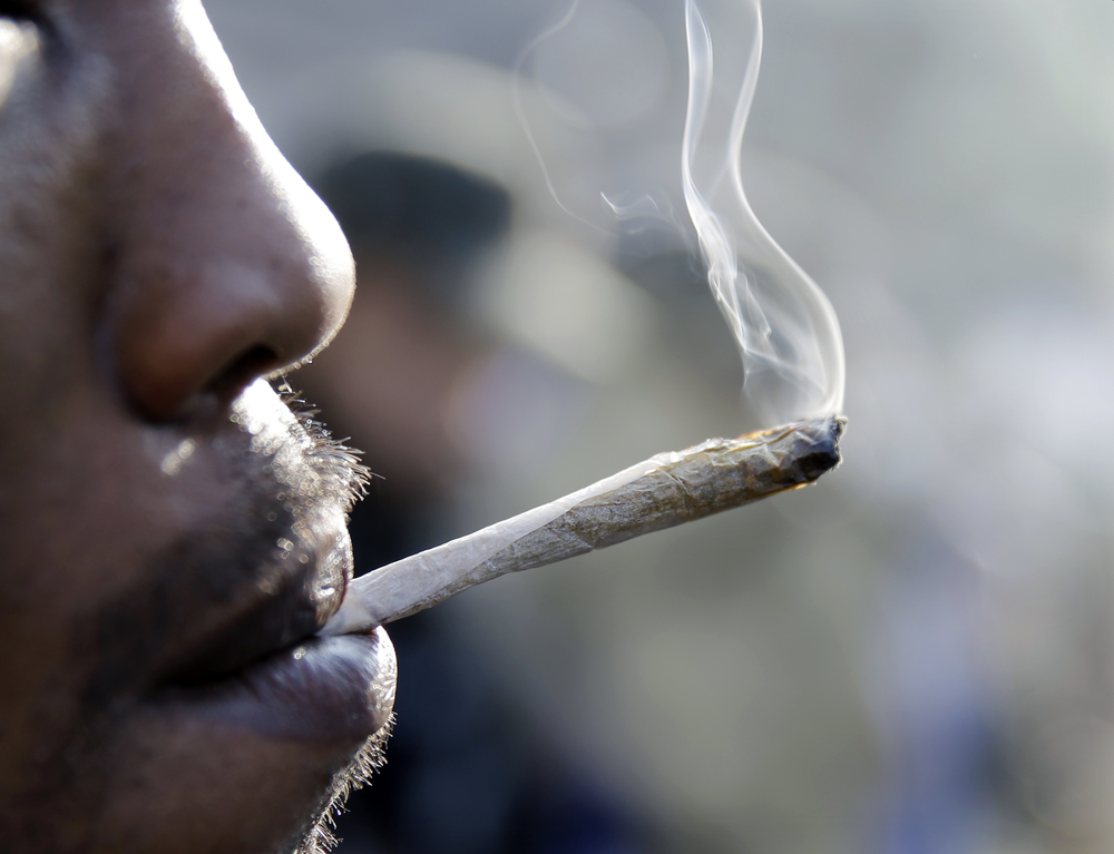 A man smokes a marijuana cigarette as a large group gathered near the New Jersey Statehouse to show their support for legalizing marijuana Saturday, March 21, 2015, in Trenton, N.J. (AP)