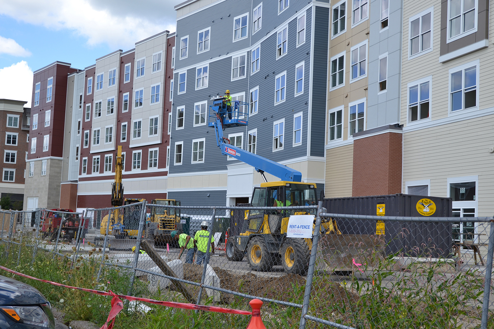 Construction crews are seen at The Oaks on the Square apartment complex in Storrs Center on Aug. 27, 2015. UConn students still awaiting apartments will be commuting or staying in hotels until the construction is completed. (Amar Batra/The Daily Campus)