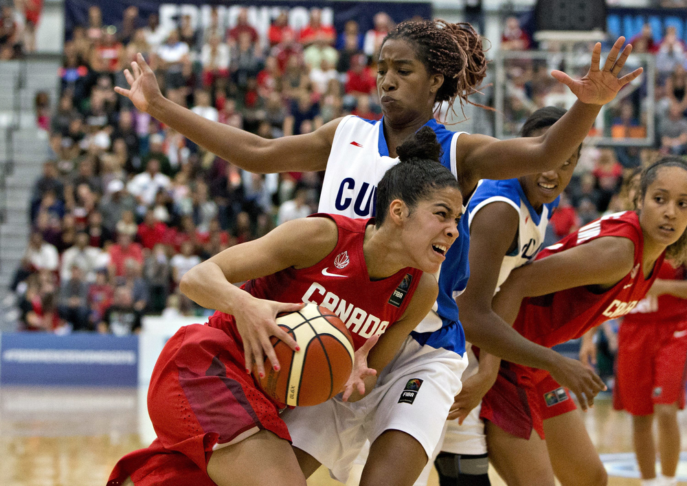 Canada's Kia Nurse, bottom, drives past Cuba's Francy Ochoa Izquierdo, top, during first half action at the 2015 FIBA Americas Women's Championship Final in Edmonton, Alberta, on Sunday, Aug. 16, 2015. (Jason Franson/The Canadian Press via AP)
