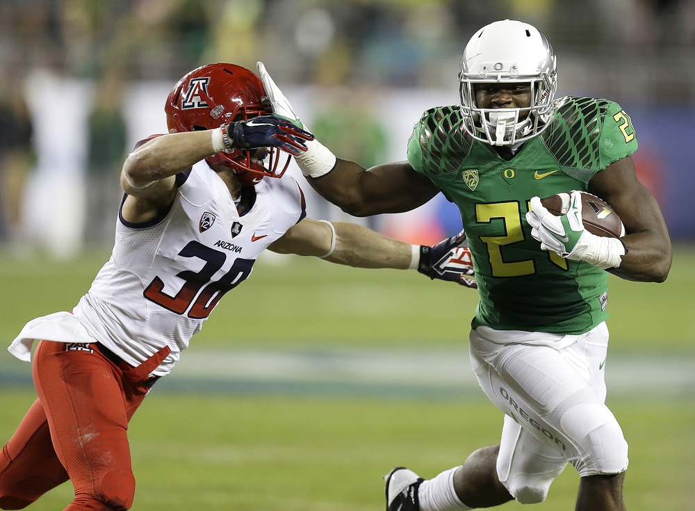 In this Dec. 5, 2014, file photo, Oregon's Royce Freeman, right, evades Arizona's Jared Tevis during the first half of a Pac-12 Conference championship NCAA college football game in Santa Clara, Calif. Just a sophomore, Freeman is already assuming a leadership role on the Ducks' offense. (Ben Margot/AP)