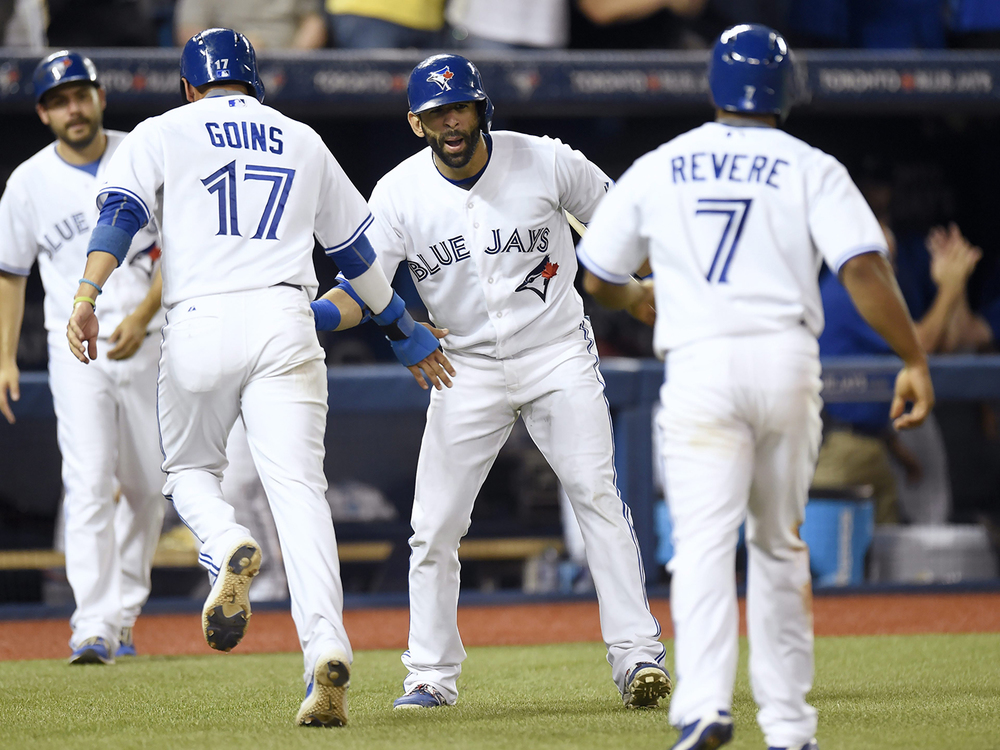 Toronto Blue Jays' Jose Bautista, center, congratulates teammates Ryan Goins, (17) and Ben Revere (7) after scoring on the Josh Donaldson's two-run triple during the fifth inning of a baseball game against the TorontoBlue Jays, Monday, Aug. 31, 2015 in Toronto. (Frank Gunn/The Canadian Press via AP)