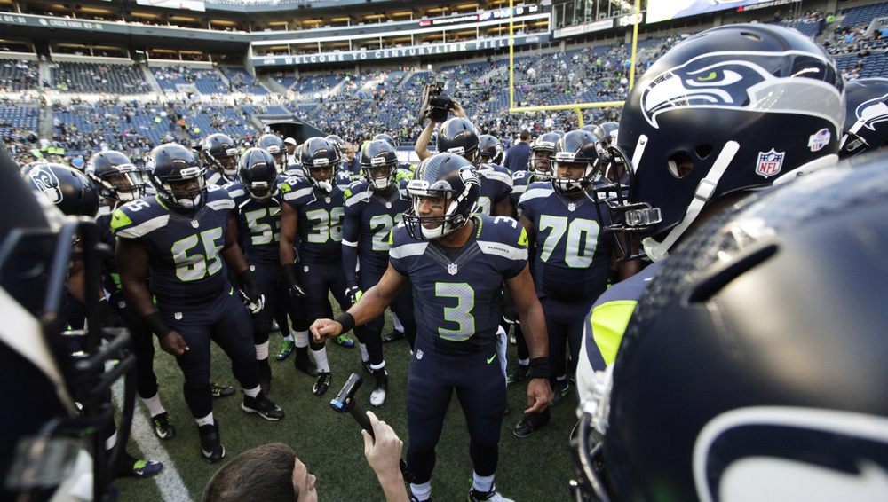 Seattle Seahawks quarterback Russell Wilson (3) leads his team in a huddle before a preseason game against the Oakland Raiders, Thursday, Sept. 3, 2015, in Seattle. (Elaine Thompson/AP)