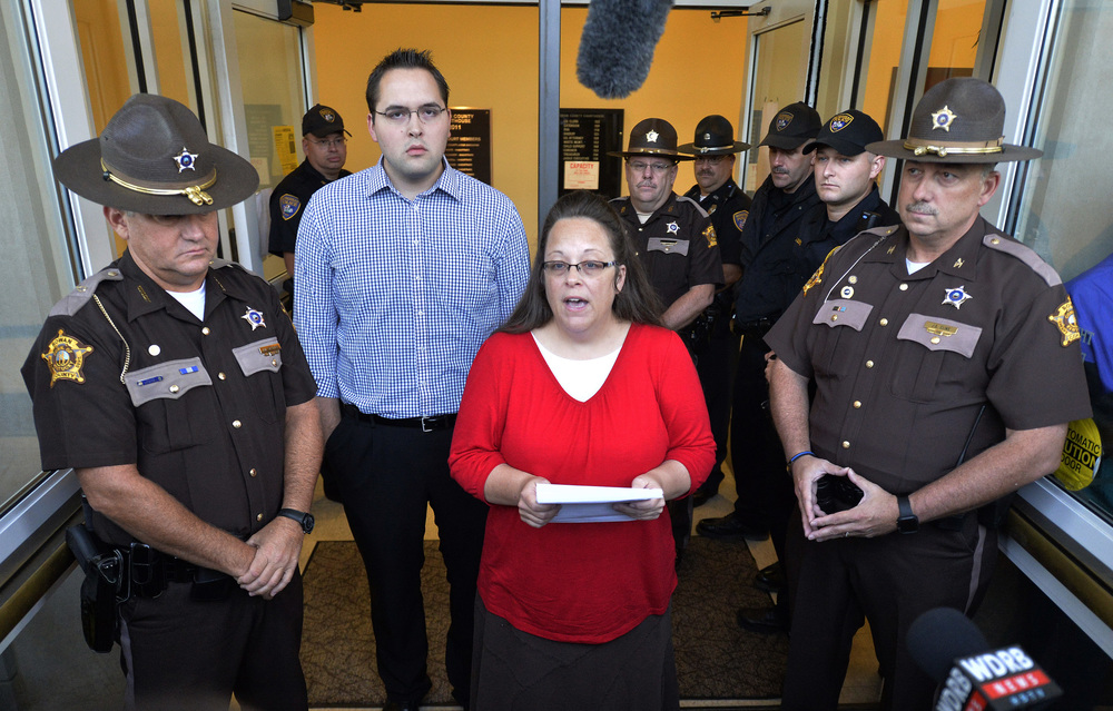 Surrounded by Rowan County Sheriff's deputies, Rowan County Clerk Kim Davis, center, with her son Nathan Davis standing by her side, makes a statement to the media at the front door of the Rowan County Judicial Center in Morehead, Kentucky, Monday, Sept. 14, 2015. Davis announced that her office will issue marriage licenses under order of a federal judge, but they will not have her name or office listed. (Timothy D. Easley/AP)