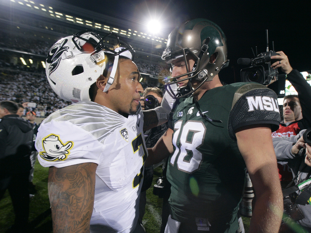 Oregon quarterback Vernon Adams Jr., left, and Michigan State quarterback Connor Cook (18) talk following an NCAA college football game, Saturday, Sept. 12, 2015, in East Lansing, Michigan. Michigan State won 31-28. (Al Goldis/AP)