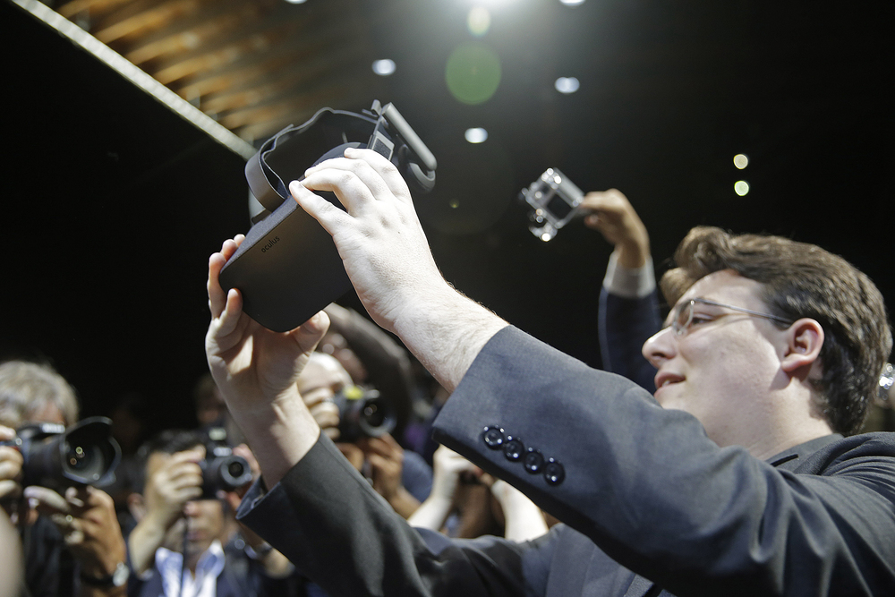 In this June 11, 2015 file photo, Oculus founder Palmer Luckey holds up the new Oculus Rift virtual reality headset for photographers following a news conference, in San Francisco. (Eric Risberg/AP)
