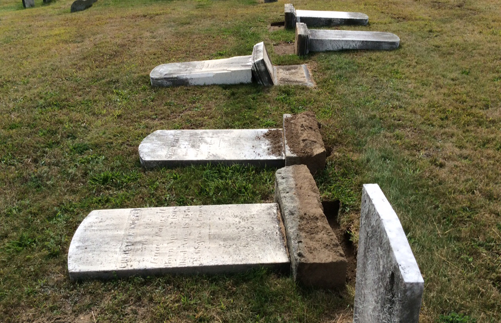 In this photo, vandalized gravestones are pictured in the Storrs Cemetary in Storrs, Connecticut. The cemetery, located on the north end of campus, is 150 years old and contains gravestones dating back to the 1800s. (Courtesy/Rene Lizee)