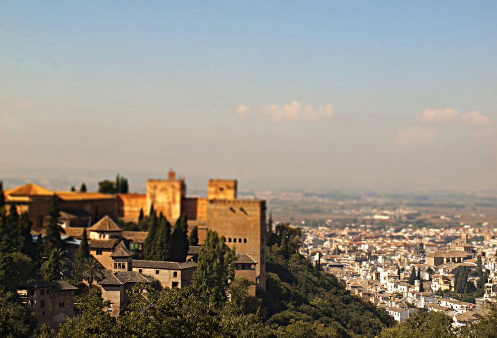 A view of Granada, Spain that shows the Alhambra, an Islamic fortress that was built in the 11th century and is currently Spain's number one tourist attraction, rising high in the hills on the left. (Kevin Poh/Flickr).