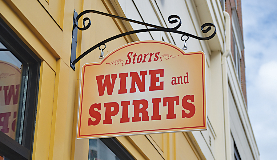 In this photo, the Storrs Wine and Spirits sign hands above the storefront in Storrs Center. On Sept. 11, several students from the University of Connecticut were arrested outside Storrs Wine and Spirits for providing alcohol to minors. (Amar Batra/The Daily Campus)
