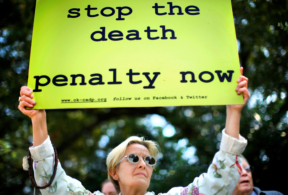 Karin Stafford, of Oklahoma City, joins a crowd of peaceful protestors who gathered in front of the Governor's Mansion in Oklahoma City, Okla., on Wednesday, Sep. 30, 2015, to keep a silent vigil as the scheduled time drew near for the execution of convicted killer Richard Glossip, currently detained at the state penitentiary in McAlester. (Jim Beckel /The Oklahoman via AP)