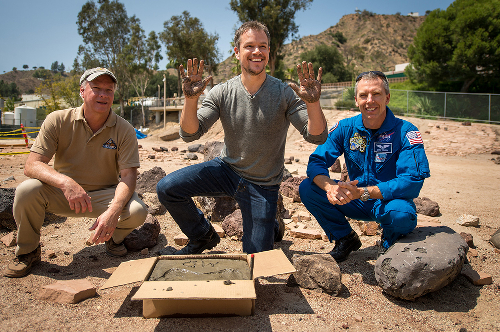 "Actor Matt Damon, who stars as NASA Astronaut Mark Watney in ""The Martian,"" smiles after making hand prints in cement at the Jet Propulsion Laboratory (JPL) Mars Yard while Mars Science Lab Project Manager Jim Erickson and NASA Astronoaut Drew Feustel look on. The movie is based on NASA data and realistically portrays what life would be like on Mars. (Bill Ingalls NASA/Flickr)."