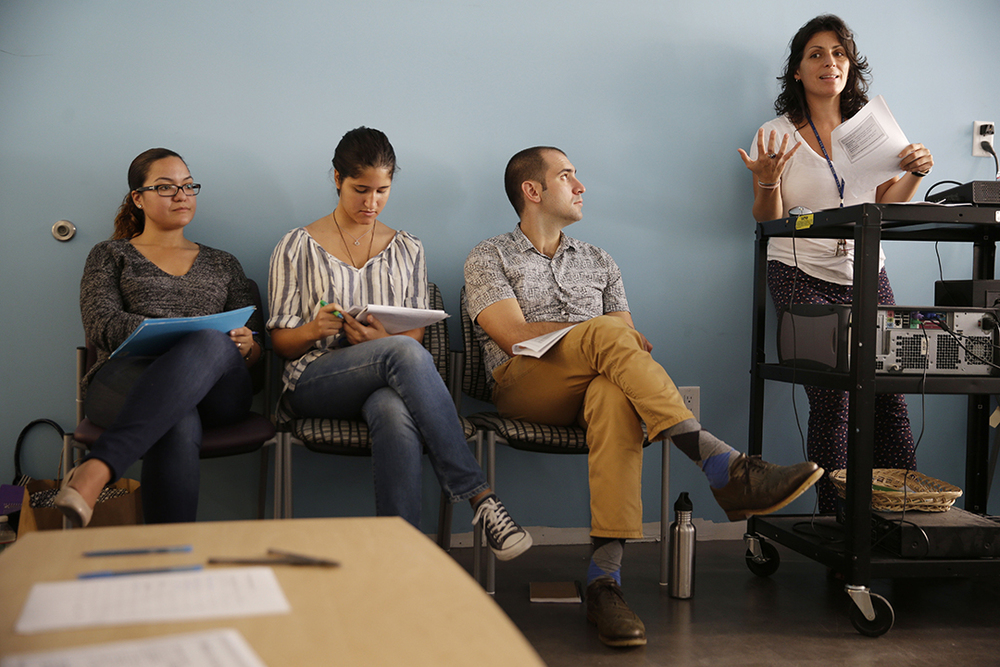 Anna Reyna, right, supervisor of the counseling department at The Door, teaches a class on adolescent development at the youth services organization, in New York. New York City is embarking on a $30 million plan to prepare to staffers at social service organizations to screen people for possible psychological problems, provide information and try to motivate them to make changes in their lives. (Seth Wenig/AP)