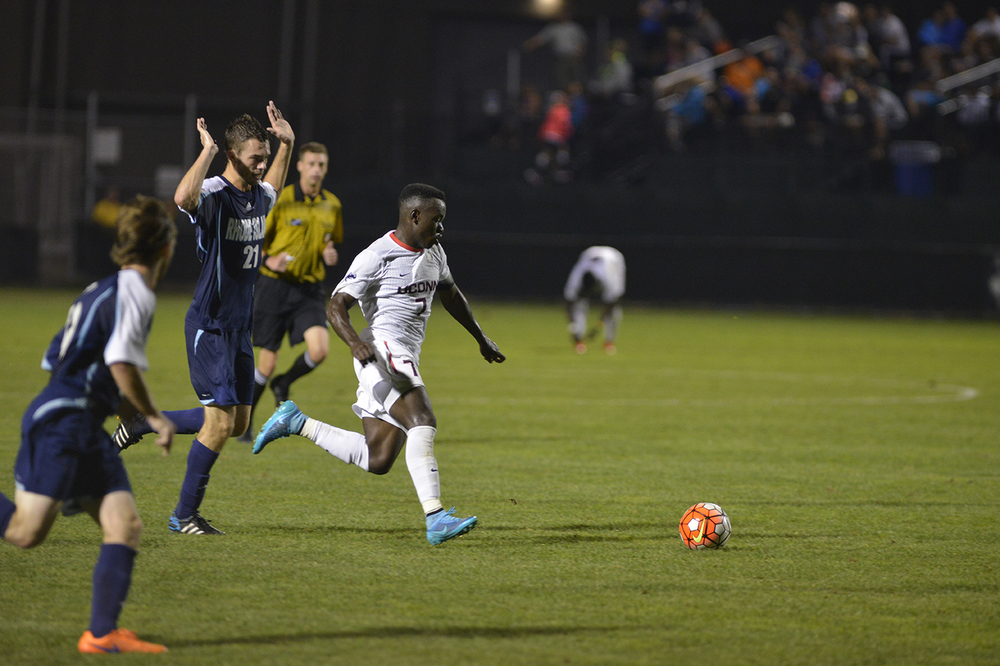 UConn junior midfielder Kwame Awuah dribbles away from a Rhode Island player during the Huskies' game against the Rams at Joseph J. Morrone Stadium in Storrs, Connecticut on Saturday, Sept. 19, 2015. (Jason Jiang/The Daily Campus)
