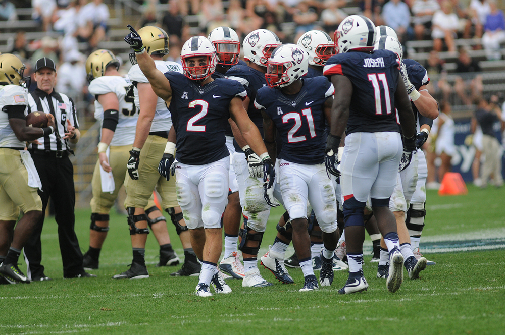 UConn football linebacker Graham Stewart (2) and other members of the Huskies' defense huddle between plays during UConn's game against Army at Pratt & Whitney Stadium at Rentschler Field in East Hartford, Connecticut on Saturday, Sept. 12, 2015. (Bailey Wright/The Daily Campus)