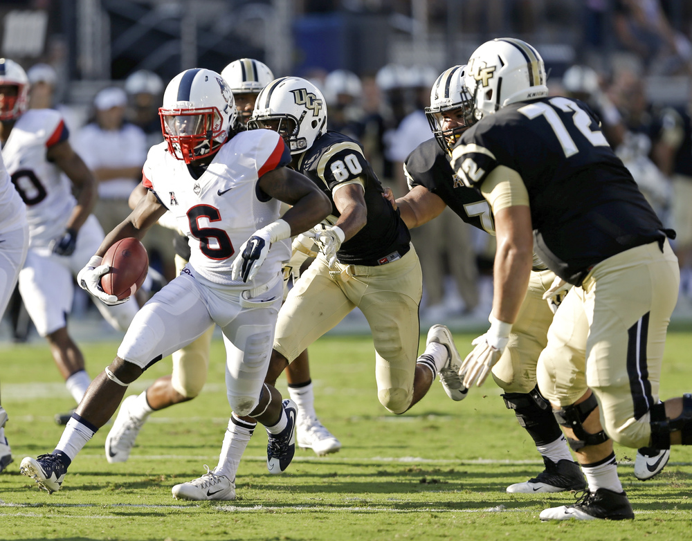Connecticut cornerback Jhavon Williams (6) runs with the ball past Central Florida wide receiver Tre'Quan Smith (80) and offensive lineman Tyler Hudanick (72) after intercepting a pass during the first half of an NCAA college football game, Saturday, Oct. 10, 2015, in Orlando, Fla. (John Raoux/AP)