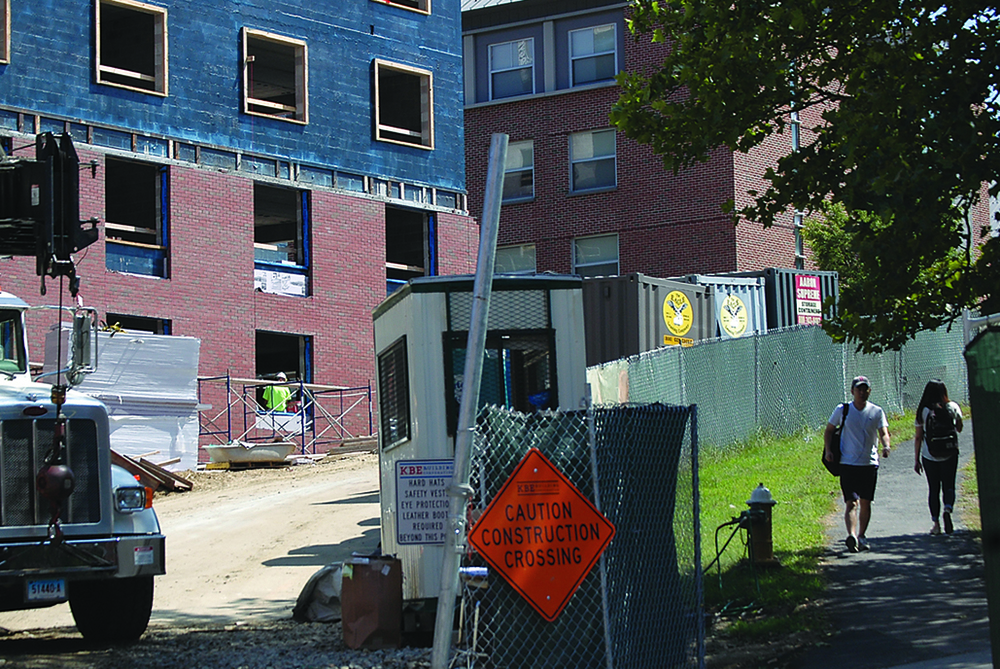 UConn students walk past construction on the new STEM residence hall near the Putnam Refectory on Sept. 1, 2015. (Erika Elechicon/The Daily Campus)