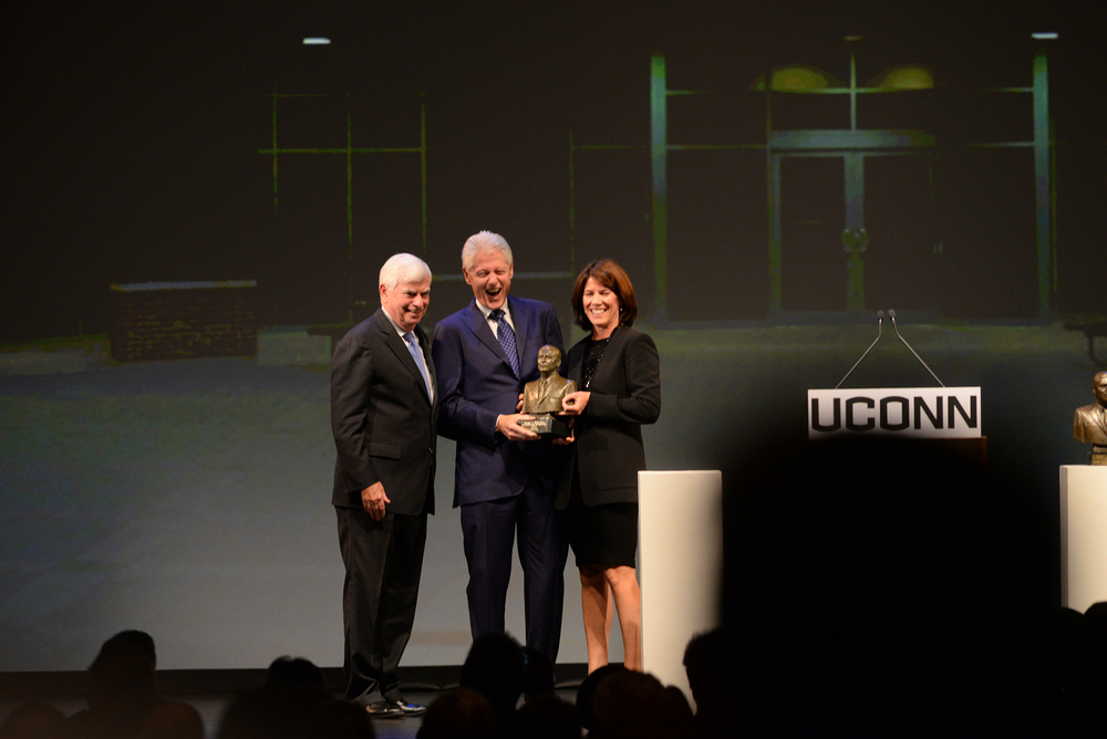 Former President Bill Clinton, center, accepts the Thomas J. Dodd Prize in International Justice and Human Rights from Helena Foulkes (right), acting chair, national advisory board of the Thomas J. Dodd Research Center and former Connecticut Sen. Chris Dodd (left) at the Jorgensen Center for the Performing Arts in Storrs, Connecticut on Thursday, Oct. 15, 2015. (Ashley Maher/The Daily Campus)