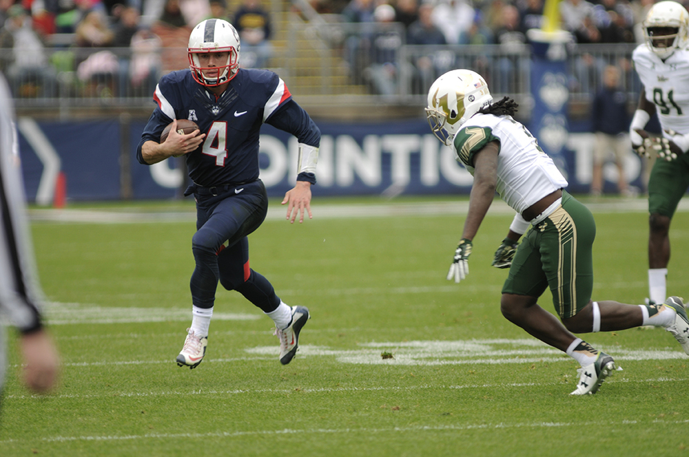 UConn quarterback Bryant Shirreffs running with the ball against South Florida in UConn's homecoming game. He finished the game with over 100 rushing yards. (Bailey Wright/The Daily Campus)