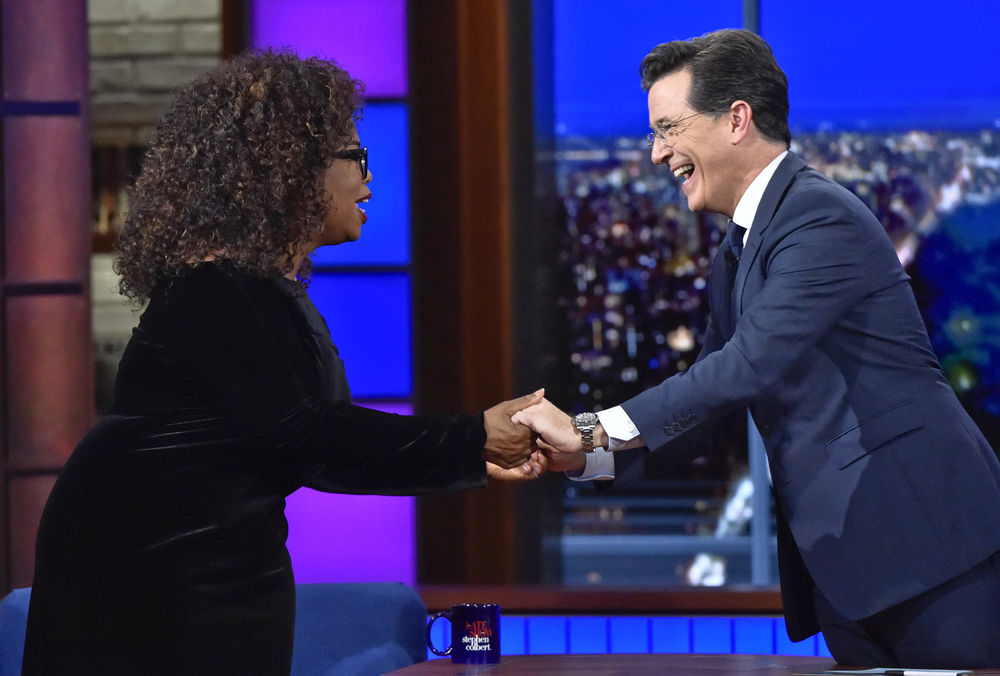 "In this photo provided by CBS, host Stephen Colbert, right, welcomes Oprah Winfrey, the chairman and chief executive officer of OWN, to the ""Late Show with Stephen Colbert"" in New York, Thursday, Oct. 15, 2015. (John Paul Filo/CBS via AP)"